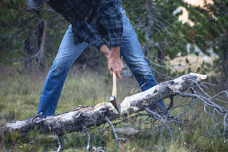 Man Cutting Wood with Hatchet by MEGHAN PINSONNEAULT for Stocksy United