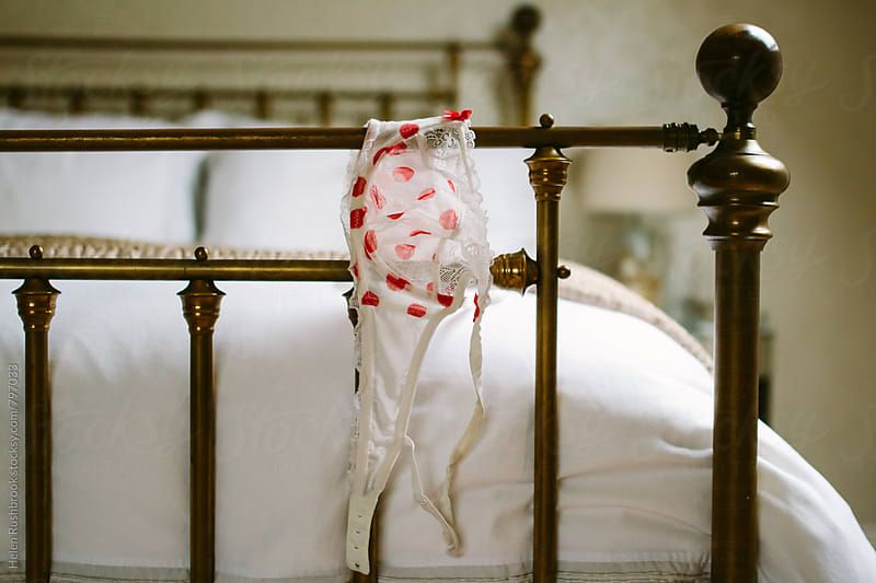Red and white polka dot lingerie draped over a brass bed. by Helen Rushbrook for Stocksy United
