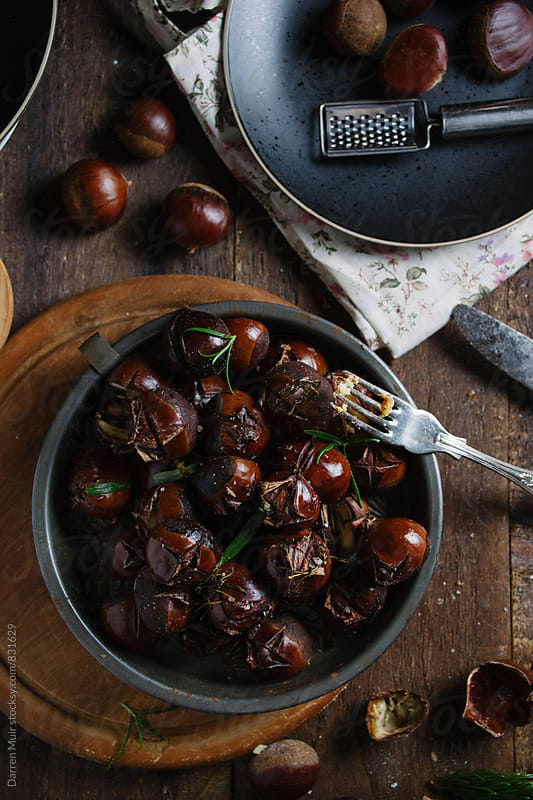 Overhead shot of a side dish of roasted chestnuts with salt and rosemary in a rustic setting. by Darren Muir for Stocksy United