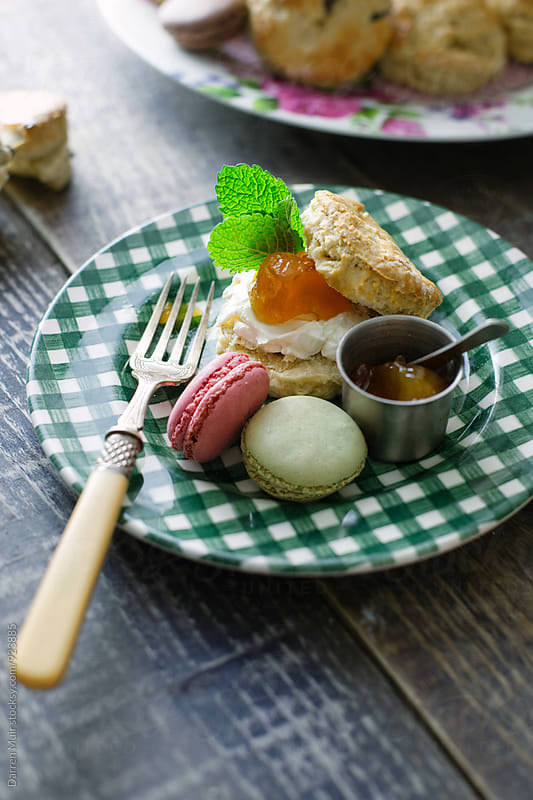 A scone with cream and apricot jam, and a couple of macarons on a green gingham plate. by Darren Muir for Stocksy United
