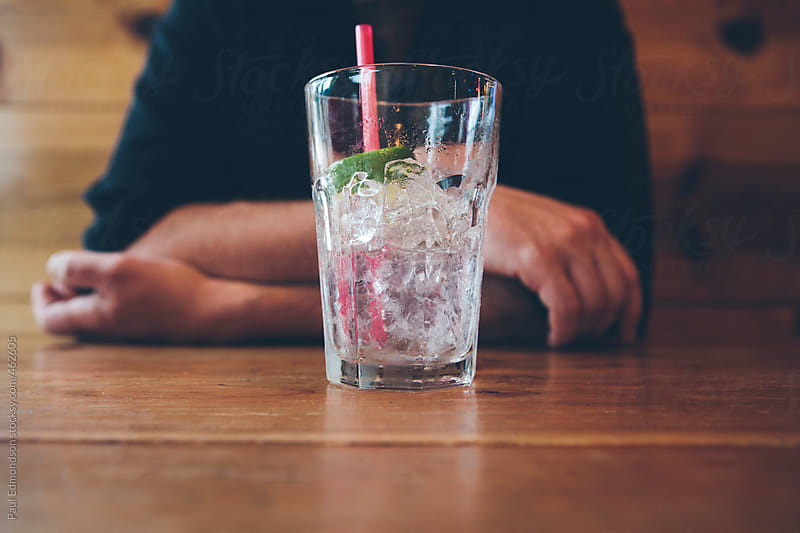 Man sitting at bar with empty cocktail, focus on beverage by Paul Edmondson for Stocksy United