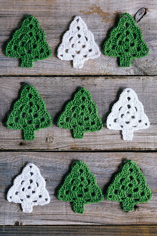 Green and White Crocheted Christmas Trees on rustic wood background - vertical by Jacqui Miller for Stocksy United