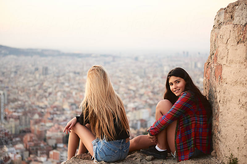 Two young girlfriends sitting against of summer cityscape by Guille Faingold for Stocksy United