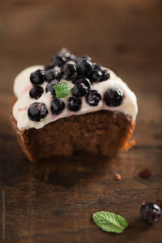 mini chocolate cake garnished with whipped cream and blueberries by Laura Adani for Stocksy United