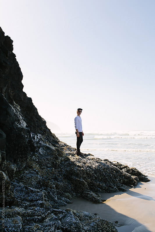 Man standing on a rocky bit of land on the coast by KATIE + JOE for Stocksy United