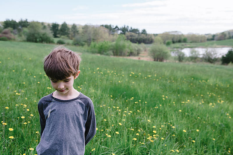 Little boy stands in field with grass in his mouth by Cara Dolan for Stocksy United