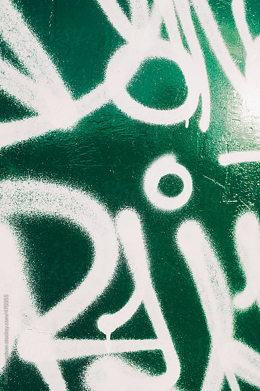 White spray painted graffiti on green metal container by Paul Edmondson for Stocksy United