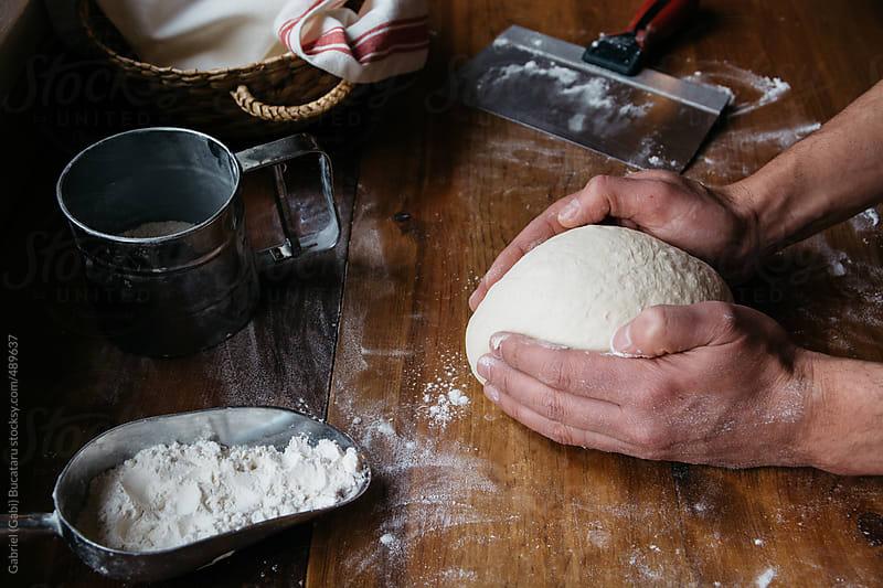 Baker's hands shaping bread dough by Gabriel (Gabi) Bucataru for Stocksy United