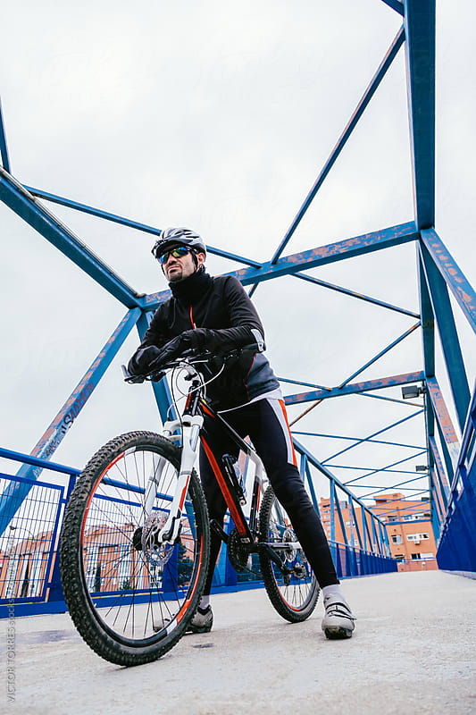 Mountain Bike Rider Posing in an Urban Scenery by VICTOR TORRES for Stocksy United