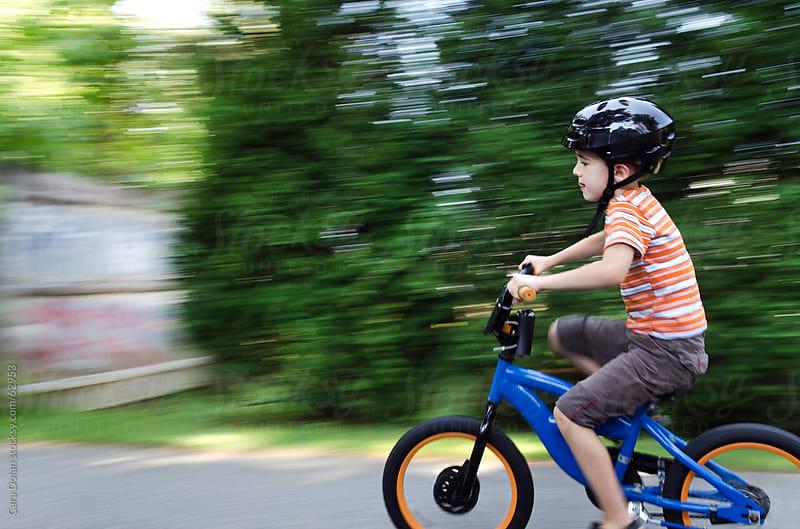 Boy wearing helmet speeds by on his bicycle by Cara Slifka for Stocksy United