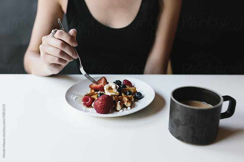 person eating waffle with fruit and butter and cup of coffee on table by Nicole Mason for Stocksy United