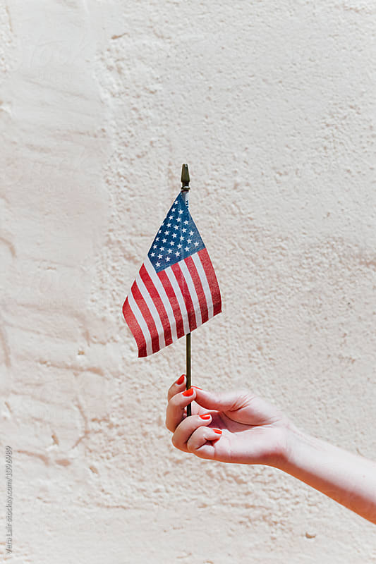 Woman hand holding a small american flag by Vera Lair for Stocksy United