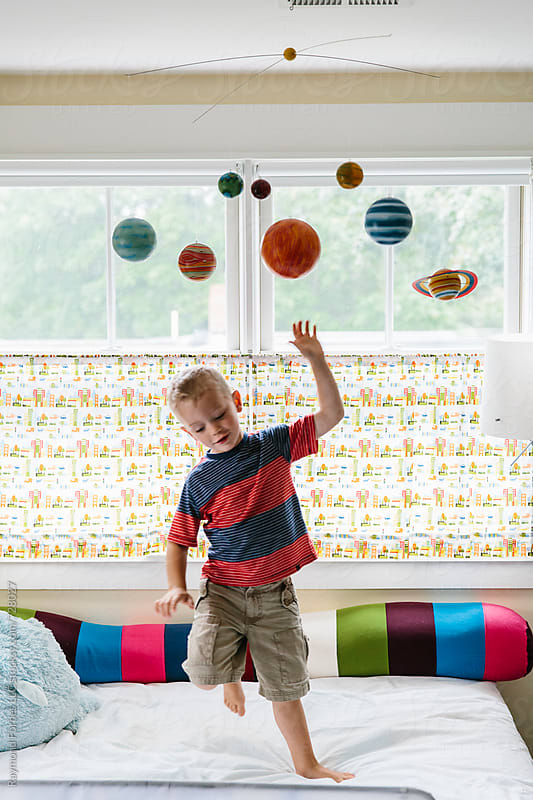 Child Playing with Solar System Mobile by Raymond Forbes LLC for Stocksy United