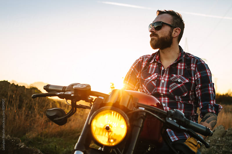 wild, young and free - casual bearded biker with sunglasses sitting on his bike at sunset by Leander Nardin for Stocksy United
