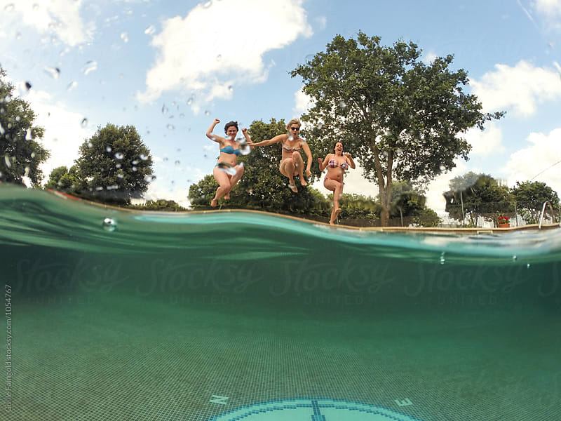 Three girlfriends jumping in pool by Guille Faingold for Stocksy United