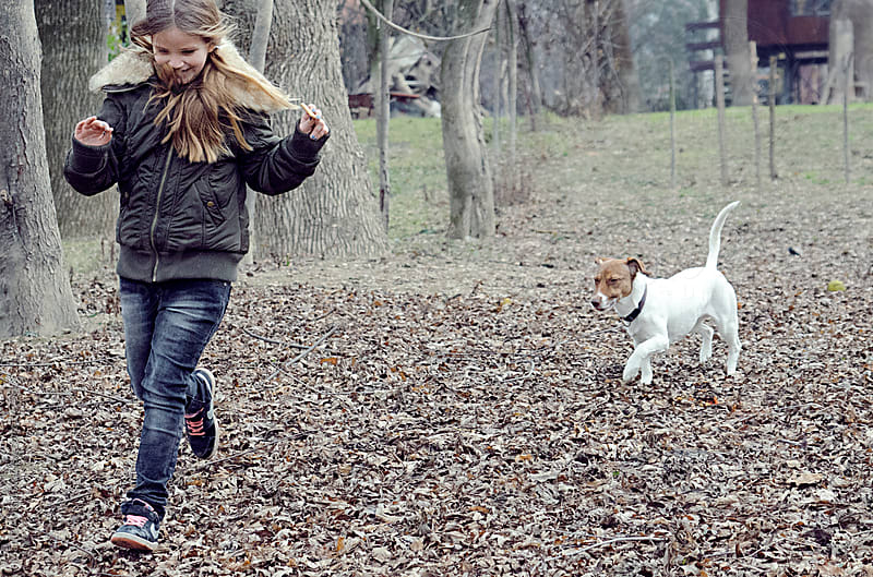 Girl is running ,playing in nature with a little white dog by Marija Anicic for Stocksy United