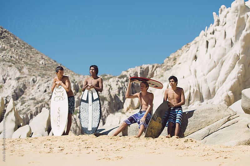 A group of young surfers sitting on a beach looking out into the water by Ania Boniecka for Stocksy United