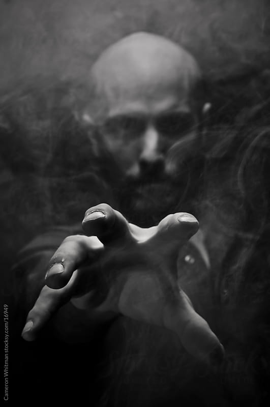 Scary Man Reaching Out Through The Smoke And Darkness  by Cameron Whitman for Stocksy United