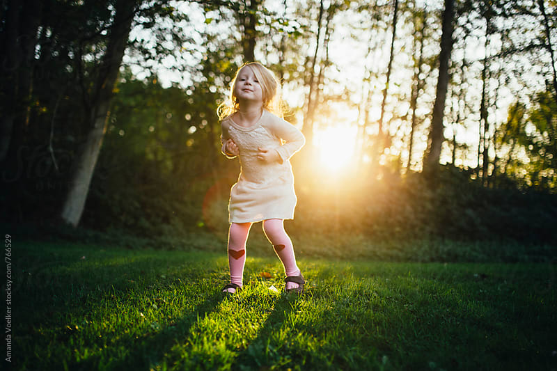 Little girl dances with conviction in the golden light by Amanda Voelker for Stocksy United