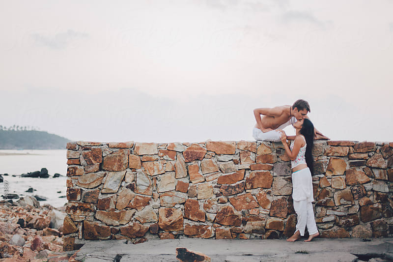 In love couple kissing on the stone wall by the sea by Nabi Tang for Stocksy United
