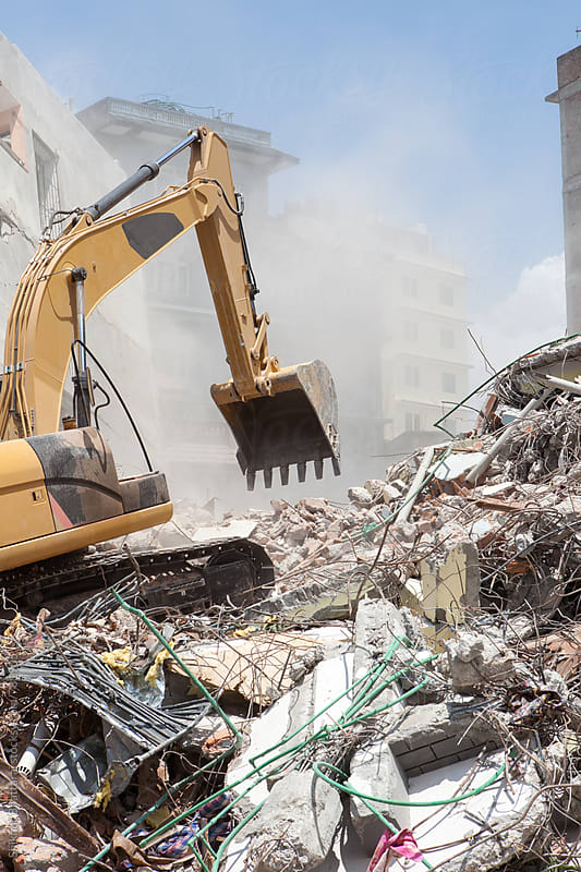 An excavator clearing off debris of a fallen building. by Shikhar Bhattarai for Stocksy United