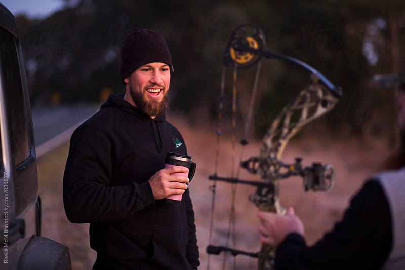 Man admiring hunting bow by Reece McMillan for Stocksy United