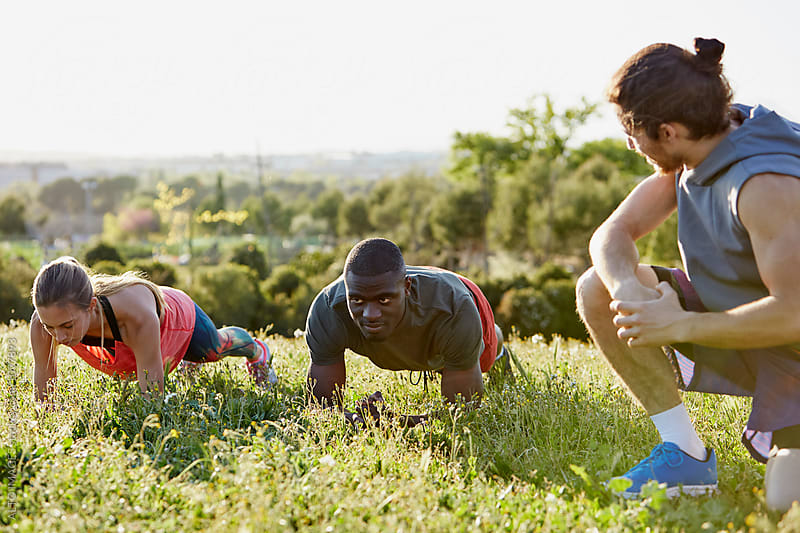 Instructor Watching Athletes Doing Push-Ups In Park by ALTO IMAGES for Stocksy United