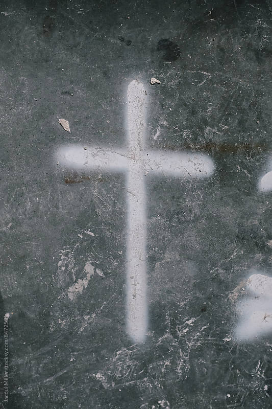 Cross painted on messy concrete floor by Jacqui Miller for Stocksy United