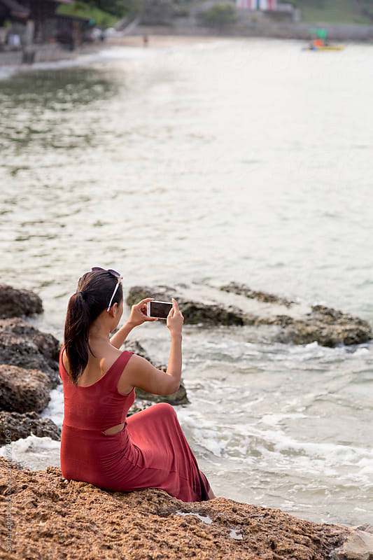 Beautiful asian girl taking photo with smart phone by the sea  by Soren Egeberg for Stocksy United