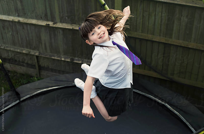 Girl happily jumping on a trampoline by CHRISTINA K for Stocksy United