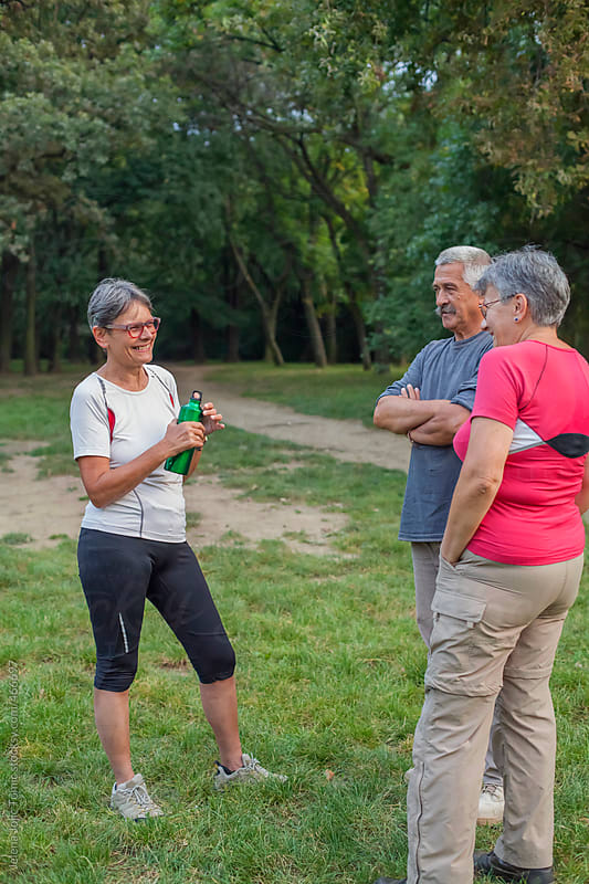 Seniors chatting in the park by Jelena Jojic Tomic for Stocksy United