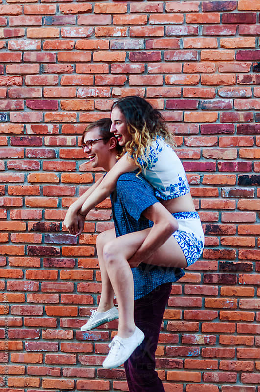 A young couple on a piggy back ride by Chelsea Victoria for Stocksy United