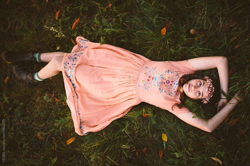 Dreamy girl lays in grassy field with a flower crown in her hair by HOWL for Stocksy United