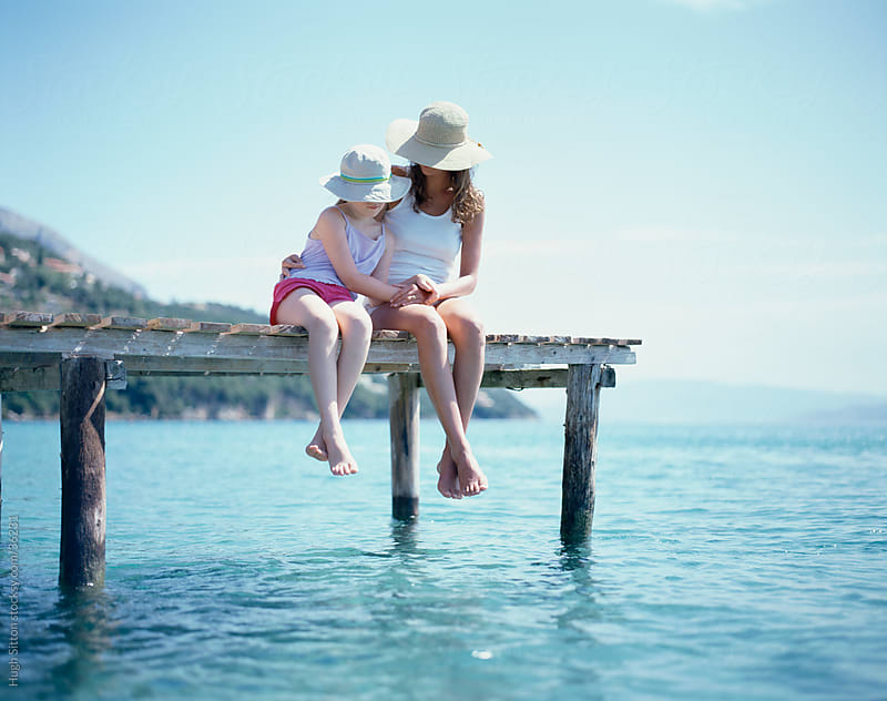 Mother and Daughter together on jetty. by Hugh Sitton for Stocksy United