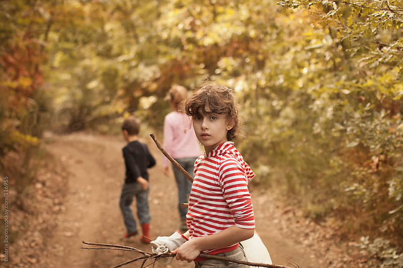 KIds walking in the forest, one of them turns around looking at camera by Beatrix Boros for Stocksy United