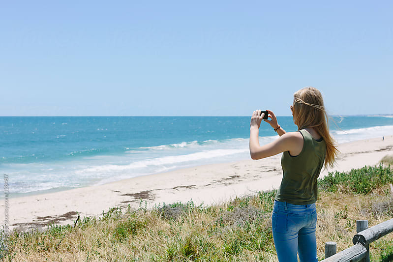 Teenage girl using a cell phone to take a photograph of the ocean by Jacqui Miller for Stocksy United