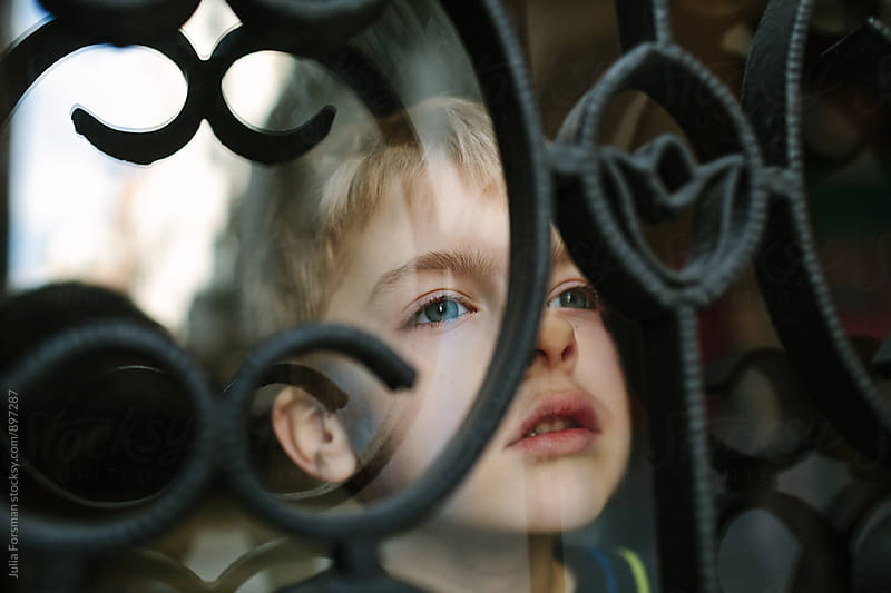 Blonde boy looks up out of barred window. by Julia Forsman for Stocksy United