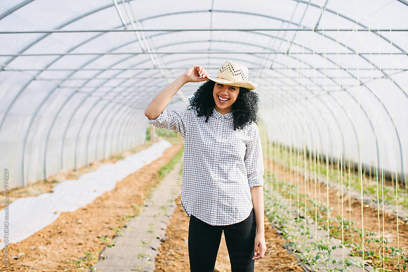 Smiling entrepreneur woman in a big greenhouse. by BONNINSTUDIO for Stocksy United