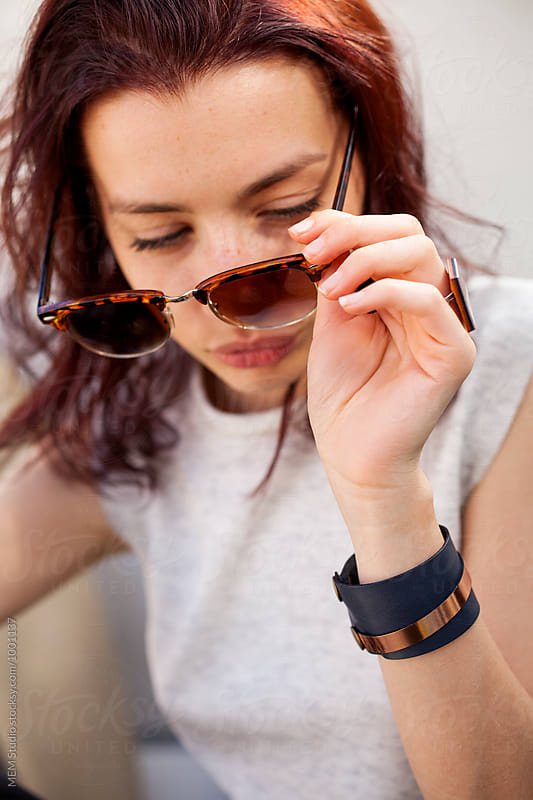 Portrait of a young woman with sunglasses by MEM Studio for Stocksy United