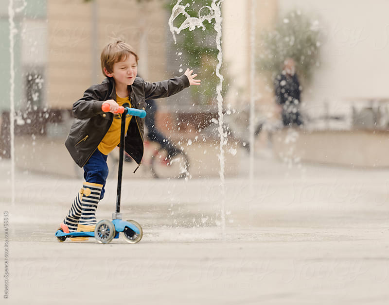 Boy riding scooter through water spray by Rebecca Spencer for Stocksy United