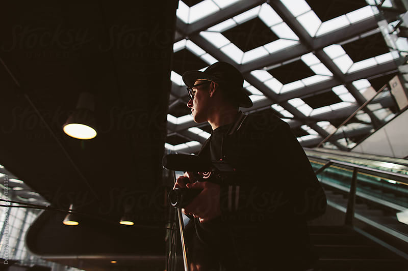 Creative man filming in an urban environment. by Denni Van Huis for Stocksy United