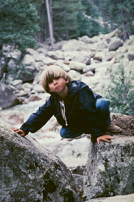 Young boy climbing on rocks by Juri Pozzi for Stocksy United
