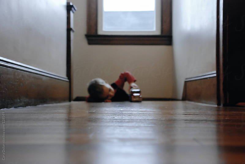 Toddler boy rolls a toy truck around on the floor by Cara Dolan for Stocksy United