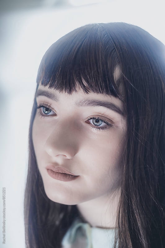 Portrait of a a beautiful young girl with dark hair and blunt bangs by Rachel Bellinsky for Stocksy United