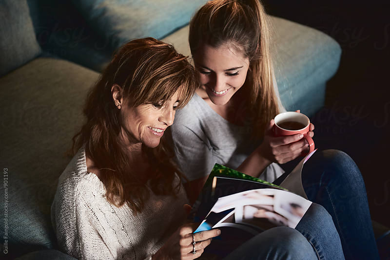 Mother and daughter reading magazine by Guille Faingold for Stocksy United