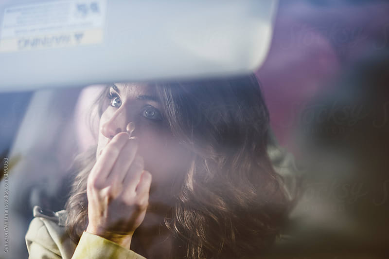 Pretty woman applying makeup in the car  by Cameron Whitman for Stocksy United