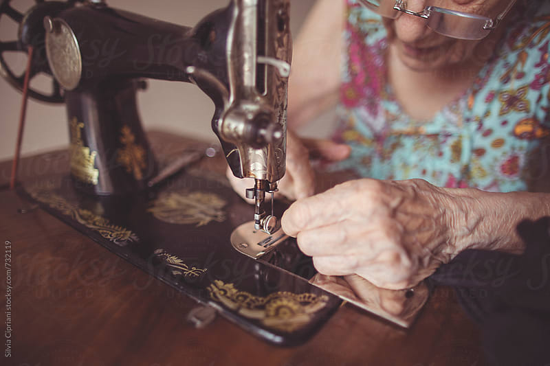 Grandma working at the sewing machine by Silvia Cipriani for Stocksy United