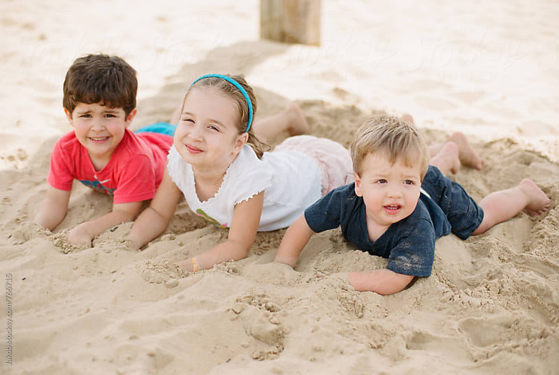 Three young children laying in sand by Jakob for Stocksy United