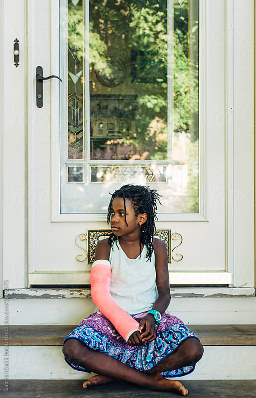 Black girl with pink cast sitting on steps by Gabriel (Gabi) Bucataru for Stocksy United