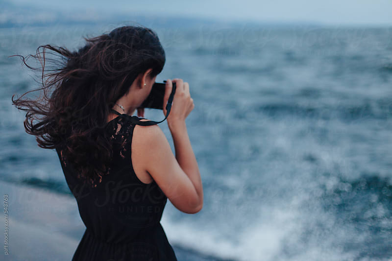 Back of a young woman taking a picture of the sea by paff for Stocksy United